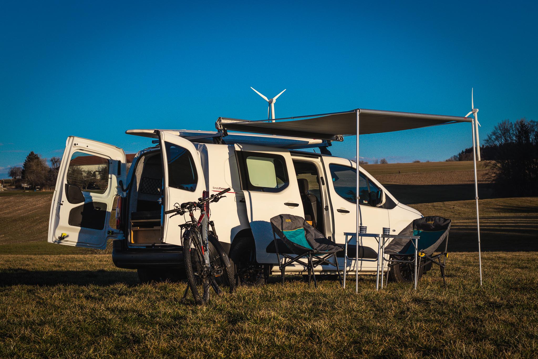 SimplyCamper mit Campingstühlen und -tisch